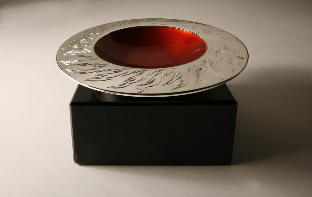"<a href=""/jewellery/ange-view-elements-spinning-bowl-fire-150mm-diam-brittania-silver-hand-engraved-orange"">Ange view: ELEMENTS SPINNING BOWL - FIRE 150mm diam. Brittania Silver, Hand Engraved, Orange enamel. Photo Andra Nelki</a>"