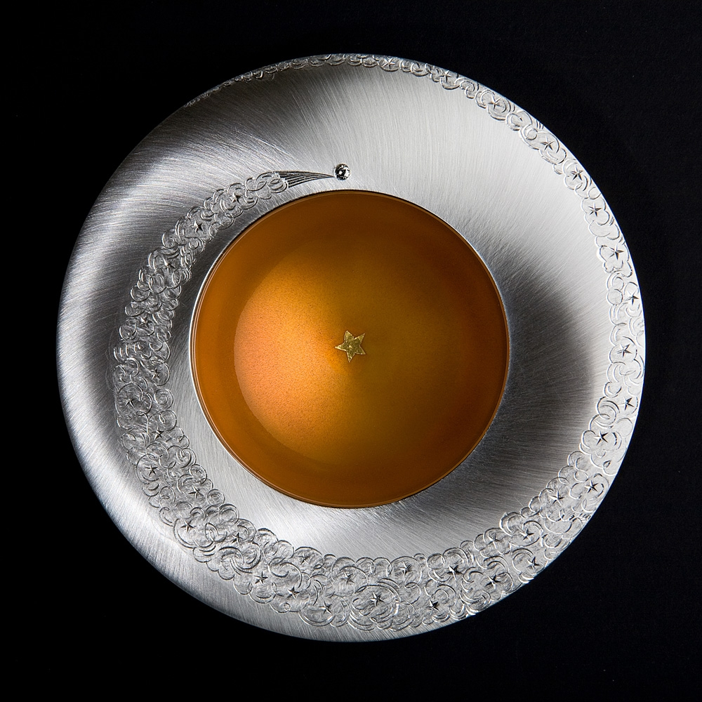 "<a href=""/jewellery/spinning-comet-bowl-day-2009-silver-hand-engraved-set-grey-diamond-gold-leaf-star-fired"">SPINNING COMET BOWL - DAY. 2009, Silver, hand engraved, set with grey diamond, gold leaf star fired into yellow/ orange enamel. 110 mm diam. Photo : Simon B Armitt</a>"